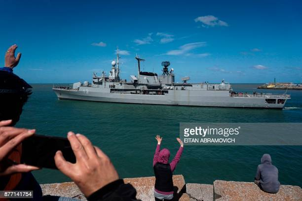 People wave at Argentina's Navy destroyer ARA Sarandi sailing off to take part in the search of missing submarine ARA San Juan from the north...