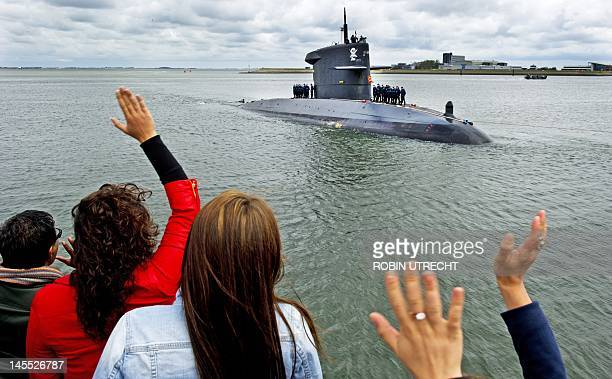 People wave at the Dutch submarine 'Hr Ms Dolfijn' in the harbor of Den Helder on June 1 2012 The submarine returned after patrolling off the coast...