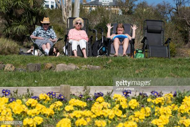 People wave at the photographer as they relax in the sun in Cliff Gardens in Westcliff on March 30, 2021 in Southend, United Kingdom. Despite todays...