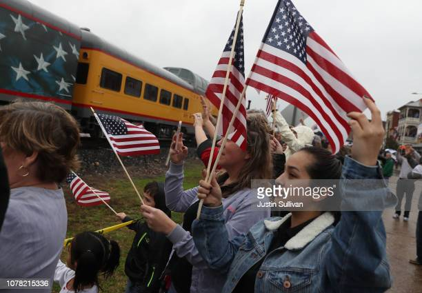People wave at the train carrying the casket of former US President George HW Bush to the George HW Bush Presidential Library at Texas AM University...
