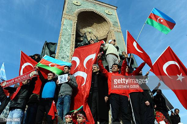 People wave Azerbaijan and Turkish flags as they demonstrate in Istanbul's central Taksim square on February 26 to commemorate the 20th anniversary...