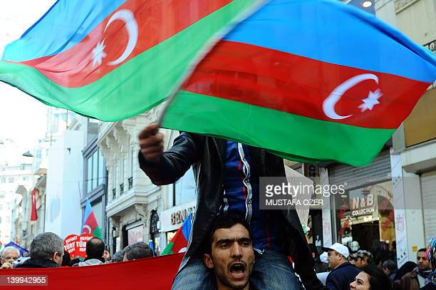 People wave Azerbaijan flags as they demonstrate in Istanbul's central Taksim square on February 26 to commemorate the 20th anniversary of the...