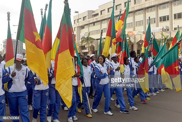 People wave Cameroon's national flag as they take part in a demonstration on February 28 2015 in downtown Yaounde against Islamist group Boko Haram...