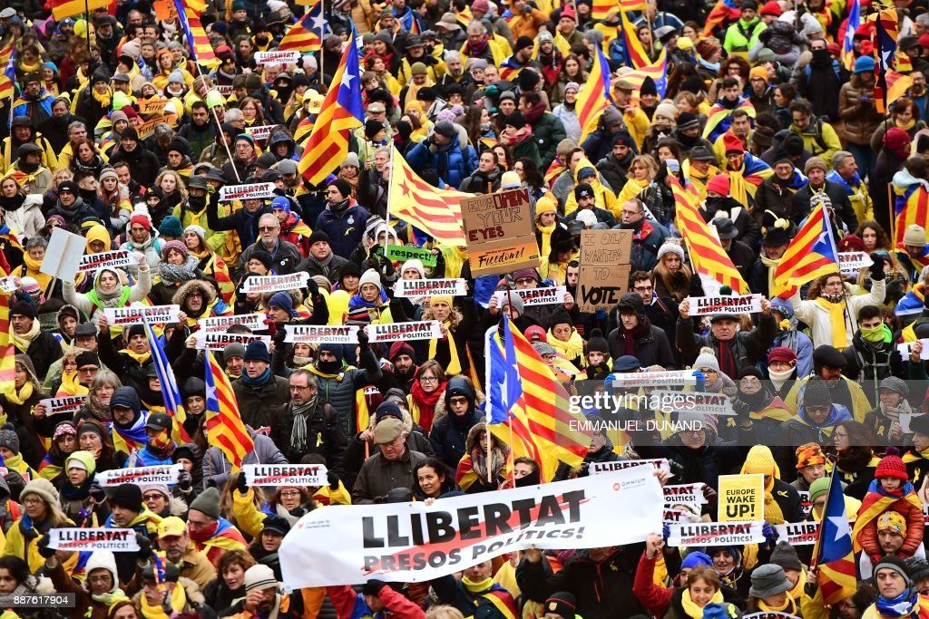 TOPSHOT - People wave Catalan 'Estelada' flags and carry signs during a pro-independence demonstration on December 7, 2017 in Brussels. Organised by pro-independence civil society organisations, protestors planned to march across Brussels calling for more democratic elections in Europe, as deposed Catalan leader Carles Puigdemont said on December 6 that he will stay in Belgium 'for now' despite Spain dropping European arrest warrants against him and four former ministers. / AFP PHOTO / Emmanuel DUNAND