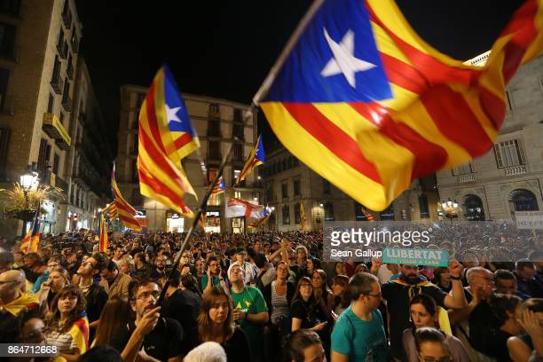 People wave Catalan independence flags after listening to a 9pm statement by Catalan regional president Carles Puigdemont while they gather in front...