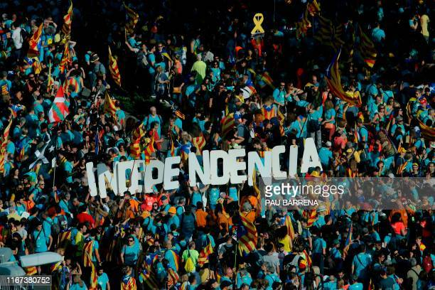 """People wave Catalan pro-independence """"Estelada"""" flags and hold a banner reading """"Independence"""" during a demonstration marking the """"Diada"""", national..."""