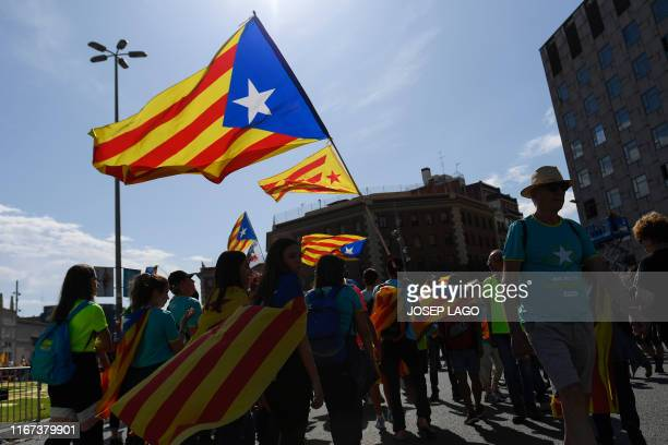 People wave Catalan proindependence Estelada flags during a demonstration marking the Diada national day of Catalonia in Barcelona on September 11...
