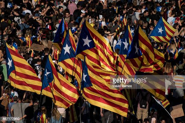 People wave Catalan ProIndependence flags known as 'Estelada' during a regional general strike to protest against the violence that marred Sunday's...