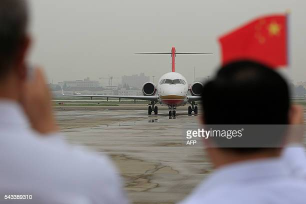 People wave Chinese flags as an ARJ21700 China's first domestically produced regional jet arrives at Shanghai Hongqiao Airport after making its first...
