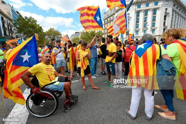 People wave 'Esteladas' as they gather before a proindependence demonstration on September 11 2017 in Barcelona during the National Day of Catalonia...