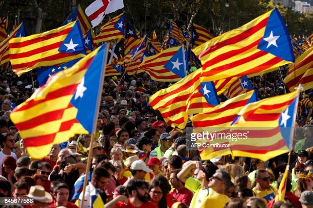 People wave 'Esteladas' as they gather during a proindependence demonstration on September 11 2017 in Barcelona during the National Day of Catalonia...