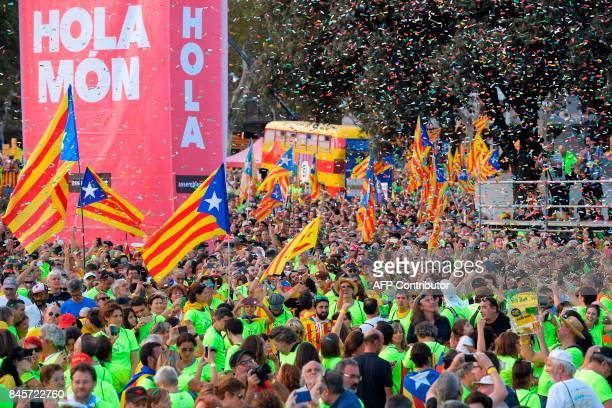 People wave 'Esteladas' during a proindependence demonstration on September 11 2017 in Barcelona during the National Day of Catalonia the 'Diada'...