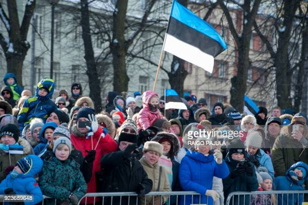 People wave Estonian flags during a military parade to celebrate 100 years since Estonia declared independence for the first time in 1918 in Tallinn...