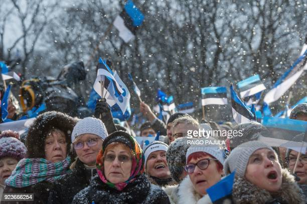 People wave Estonian flags in front of the Estonian Parliament during a festive ceremony to celebrate 100 years since Estonia declared independence...