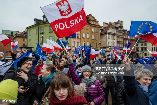 People wave European and Polish flags and sing the European anthem 'Ode to Joy' as they take part in a flash mob to protest against a new media law...