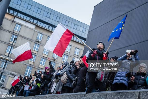 People wave European and Polish flags as they take part in a protest against a new media law in the center of Warsaw on January 9 2016 Since...