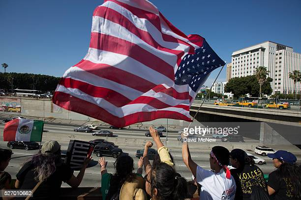 People wave flags and cheer over the 101 freeway near the Metropolitan Detention Center during one of several May Day marches on May 1 2016 in Los...