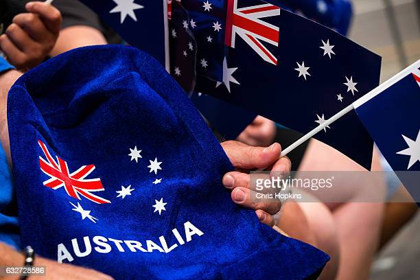 People wave flags and festive merchandise to celebrate Australia Day on January 26 2017 in Melbourne Australia Australia Day formerly known as...