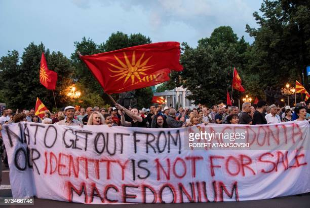People wave flags and hold a banner with the lettering 'NATO get out from Macedonia our identity is not for sale' in front of the parliament building...