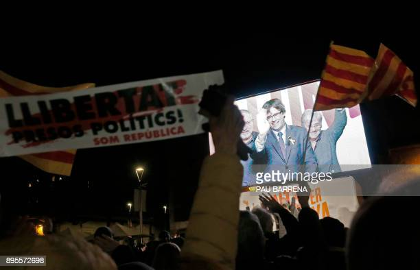 People wave flags and hold banners demanding freedom for jailed separatists leaders as they watch deposed Catalan regional president and 'Junts per...