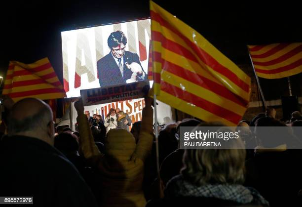 TOPSHOT People wave flags and hold banners demanding freedom for jailed separatists leaders as they watch deposed Catalan regional president and...