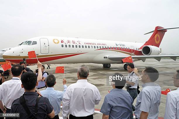 People wave flags as China's first domestic regional jet ARJ21700 arrives at Shanghai Hongqiao Airport after making its first flight from Chengdu to...