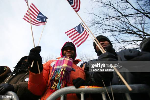 People wave flags as they gather during the inauguration of Barack Obama as the 44th President of the United States of America on the National Mall...