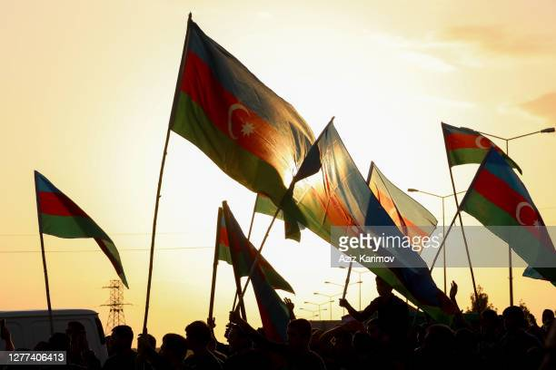 People wave flags at the funeral of a member of Azerbaijani Armed Forces who was allegedly killed during the fighting over the breakaway region of...