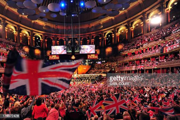 People wave flags at the Royal Albert Hall in west London on September 7 2013 during the last night of the Proms US conductor Marin Alsop became the...