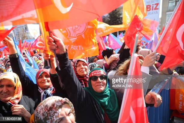 People wave flags during a campaign rally of Turkey's ruling Justice and Development Party in Ankara's district of Yenimahalle on March 14 ahead of...