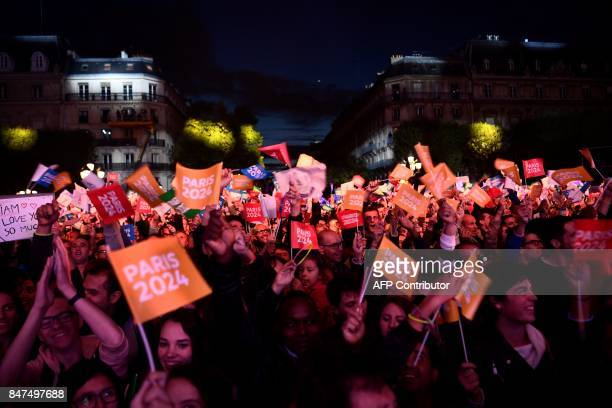 People wave flags during a concert in front of the Hotel de Ville in Paris on September 15 2017 to celebrate Paris' coronation as host of the 2024...