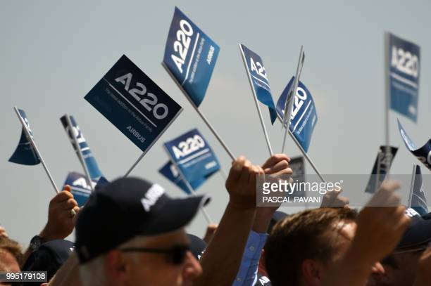 People wave flags during the presentation of the new Airbus A200300 on July 10 2018 at the Airbus delivery centre in Colomiers southwestern France
