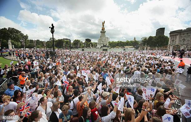 People wave flags from the crowd at the official Olympic Games handover party outside Buckingham Palace on August 24 2008 in London England Around...