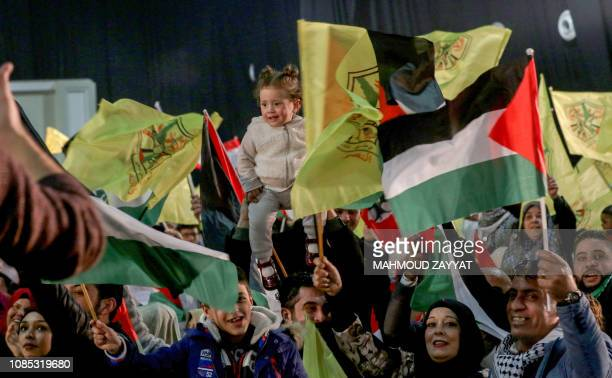 People wave flags of Palestine and Fatah as they attend a mass wedding ceremony for 150 Palestinian couples and 50 other Lebanese couples organised...