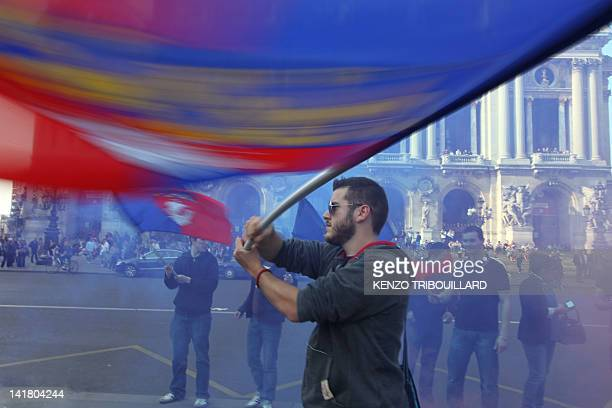 """People wave flags of Paris' city during a demonstration of the Bloc Identitaire to protest against the fact that """"Qatar buys France"""" on March 24,..."""