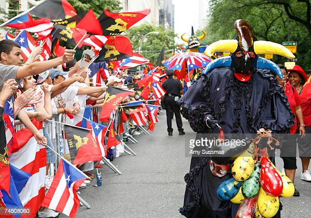People wave flags while others dress in costume during the 50th Anniversary of the National Puerto Rican Day Parade along 5th Avenue June 10 2007 in...