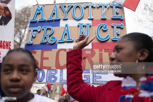 People wave French flags and shout as they take part in a rally to protest against insecurity and immigration on the French Indian Ocean island of...