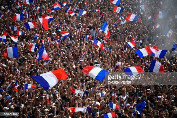 People wave French flags as they gather to watch the Russia 2018 World Cup final football match between France and Croatia on July 15, 2018 in the...