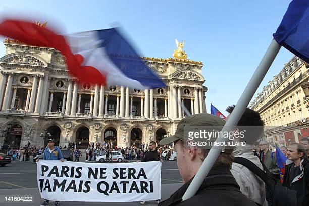 """People wave French flags during a demonstration of the Bloc Identitaire to protest against the fact that """"Qatar buys France"""" on March 24, 2012 in..."""