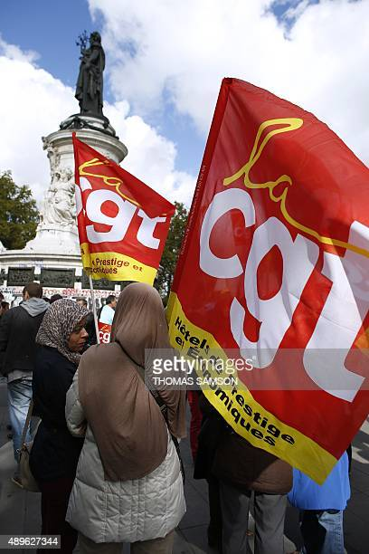 People wave French General Confederation of Labour union flags during a demonstration at the Place de la Republique in Paris on September 23 on the...