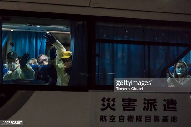 People wave from a bus carrying passengers who will board the Qantas aircraft chartered by the Australian government from the quarantined Diamond...