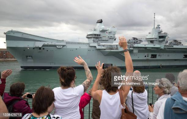 People wave from the Round Tower as the Royal Navy aircraft carrier HMS Queen Elizabeth leaves Portsmouth Naval Base as it sets sail for flight...