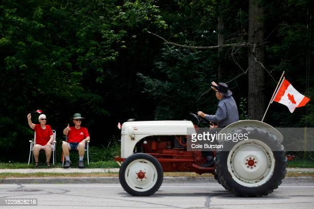People wave from their front lawns as they watch a passing Canada Day drive-by parade on July 1, 2020 in Newcastle, Canada. While most events marking...