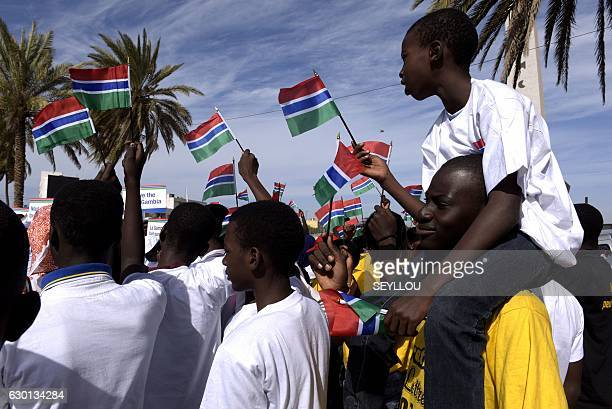 People wave Gambian flags during a protest in support of Gambia by Senegalese NGOs and civil rights groups in Dakar on December 17, 2017. Longtime...