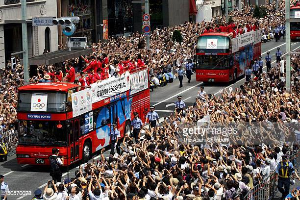 People wave hands to Japanfs Olympic medalists as their buses parade on the streets of Tokyoes upmarket Ginza district on August 20 2012 in Tokyo...
