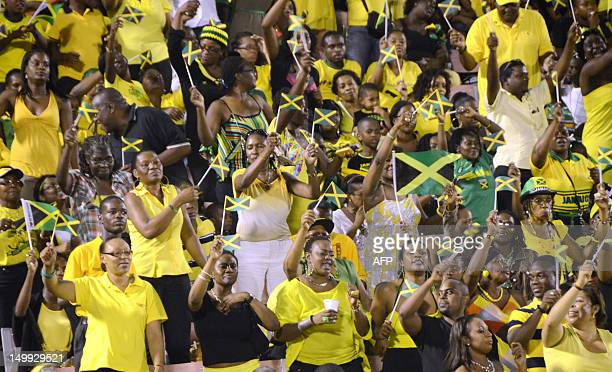 People wave Jamaican flags August 6 2012 during the Jamaica 50th Independence Grand Gala celebration at the National Stadium in Kingston Jamaica...