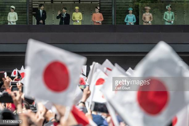 People wave Japanese flags as Emperor Naruhito accompanied by his wife Empress Masako and other members of the Japanese royal family waves from the...