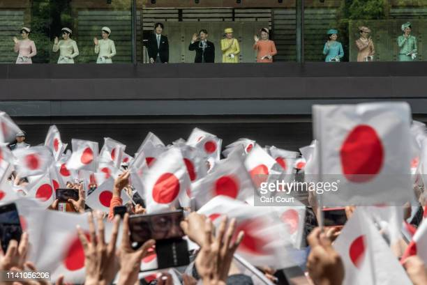 People wave Japanese flags as Emperor Naruhito of Japan waves to members of the public as his wife Empress Masako and other members of the Japanese...