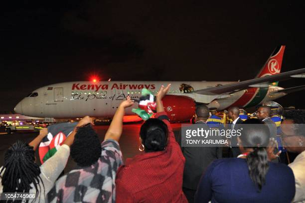 People wave Kenyan flags as a Boeing 787Dreamliner of Kenya Airways taxis out to the runway following a flagoff ceremony attended by the Kenyan...