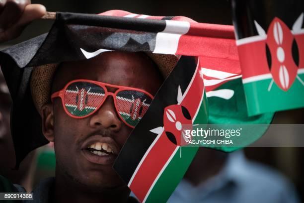 People wave Kenyan flags during the Independence Day ceremony called Jamhuri Day at Kasarani stadium in Nairobi Kenya on December 12 2017 / AFP PHOTO...